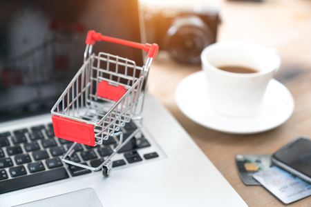 Small shopping cart on Laptop for shopping online with nature background, Technology business online concept.