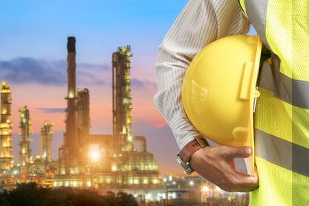 Olieraffinaderij-industrie Helm-ingenieurs voor veiligheid, staand met de details van roestvrijstalen cilindervoeringen voor de voedingsindustrie. Stockfoto