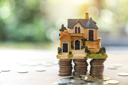 purchasing: Model of house with coins on wooden table on blurred background