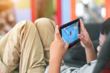 High Angle View Of Boy Using Digital Tablet For Playing Game Stock Photo
