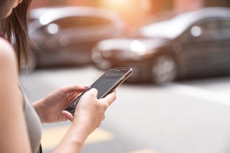휴대 전화에 택시 앱을 사용하는 여성 스톡 콘텐츠