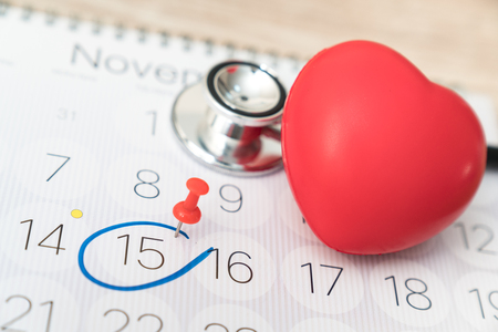 Doctor appointment on a calendar with a green push pin to remind you and important appointment.
