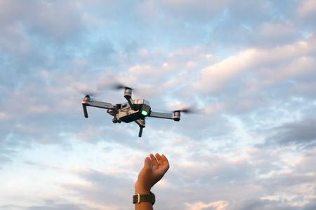 De drone en fotograaf man handen, De drone met de professionele camera neemt foto's. Stockfoto