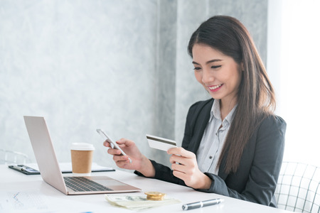 Women use laptops and mobile phones to shop online and pay by credit card.