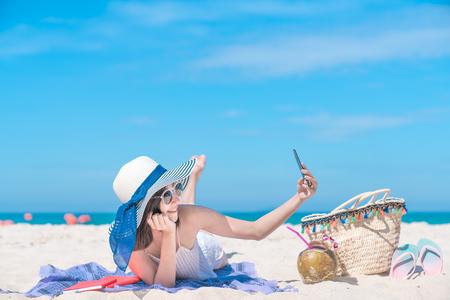ビーチでの夏の旅行でソーシャルメディアのためのスマートフォンでモバイル写真で楽しむセルフアジアの女の子との休日のスマート写真セルフポ