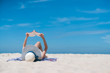 Portrait of a young brunette relaxing on the beach, reading a book Foto de archivo