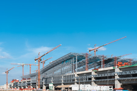 The structure of the steel roof frame with mobile crane under the building with the blue sky.