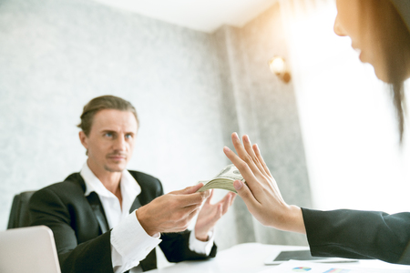 Businessman refusing money in the envelope offered by a man - anti bribery and corruption concepts