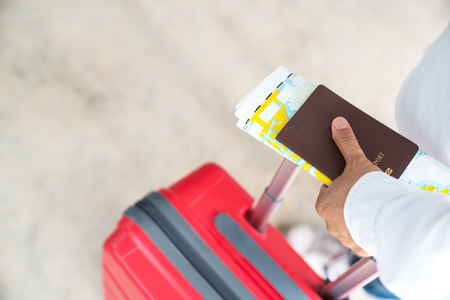 Tourists handle passports and suitcases to prepare for the trip. Stock Photo