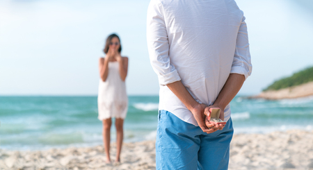 Man holding box with marriage ring making propose to his girlfriend at the beach, Love and marriage concept,