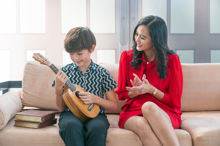 Asian son plays a Hawaiian string quartet with his mother in the house.