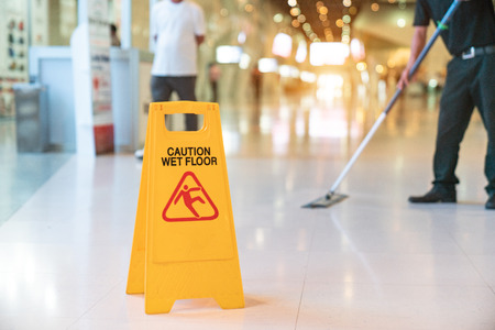 Low Section Of Worker Mopping Floor With Wet Floor Caution Sign On Floor Archivio Fotografico - 105206681