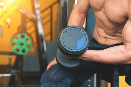 man in sportswear focused on lifting a dumbbell during an exercise