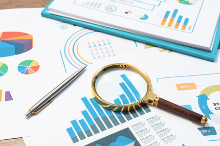 Checking financial reports. Graphs and charts. Documents and magnifying glass on gray reflection background. Stok Fotoğraf