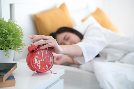 Woman turning off the alarm clock Banco de Imagens
