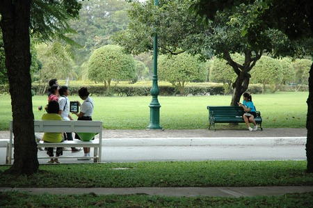 Nakhon Pathom, Thailand - November 11, 2013: Teenagers taking photo with tablet and using smartphone while relaxing in the park.