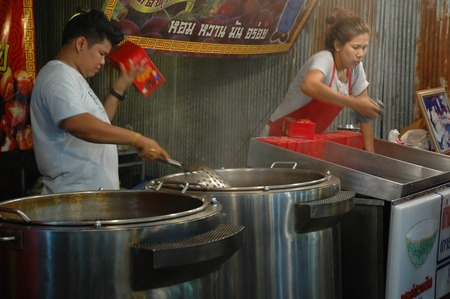 nakhon pathom: Nakhon Pathom, Thailand - November 12, 2013: Sellers are preparing roasted chestnuts for customers behind the chestnuts roaster in Wat Phra Pathom Chedi temple fair.