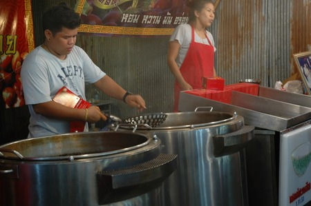 Nakhon Pathom, Thailand - November 12, 2013: Sellers are preparing roasted chestnuts for customers behind the chestnuts roaster in Wat Phra Pathom Chedi temple fair.