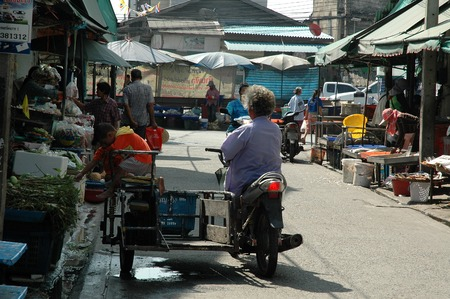 sidecar: Samut Prakan, Thailand - December 6, 2013: A grandma takes her twin grandsons on the motorcycle with sidecar with her to buy food staples at the local fresh market of Tambon Khlong Dan.