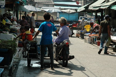 samut prakan: Samut Prakan, Thailand - December 6, 2013: A grandma with twin grandsons on the sidecar buying food staples at the local fresh market of Tambon Khlong Dan.