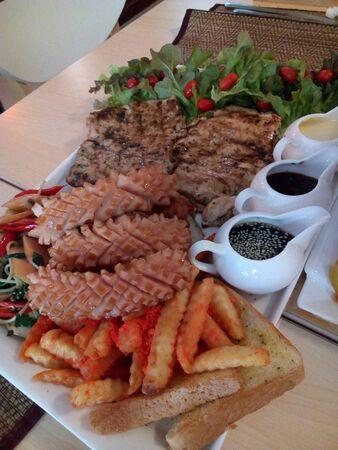 Pork Steak with Sausage and French Fries Standard-Bild