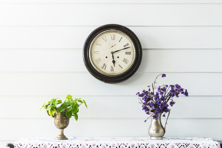 Retro home decor. Flowers and a vintage clock on a white wall shelf.