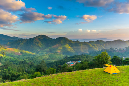 Camping orange tent on the mountain during sunrise in Chiang Rai, Thailand.