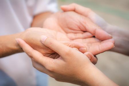 Asiatischer Senior und asiatische junge Händchen haltend.
