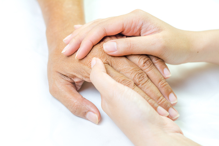 Asian senior and asian young holding hands.