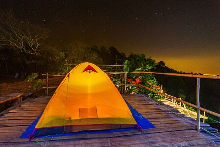 Camping orange tent at National Park in Northern,Thailand. Imagens - 140938483