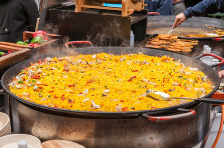 Paella rice dish in large cooking pan at market