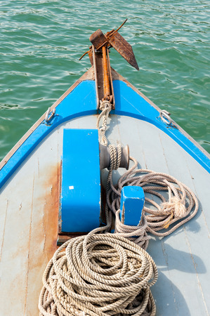 stock photographs: Rusty anchor on the front of a blue wooden boat