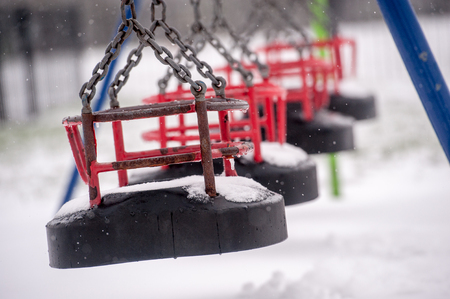 swing seat: Snow on swing seat in a childrens playground Stock Photo