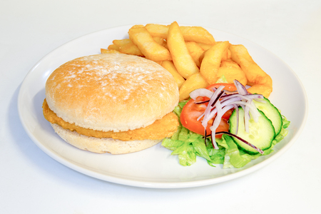 meaty: Breaded chicken burger in a bun meal with chips and salad Stock Photo