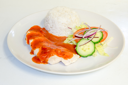 side order: Chicken dinner with rice topped with tomato sauce Stock Photo