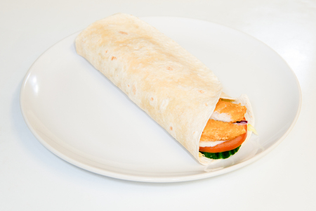 tortilla wrap: Crispy chicken and salad in a tortilla wrap on a plate
