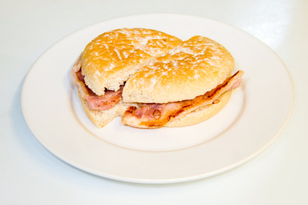 bap: Small bread bun with bacon inside cut on a plate