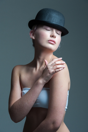 bowler hat: young lady posing in a black bowler hat with hands touching her body