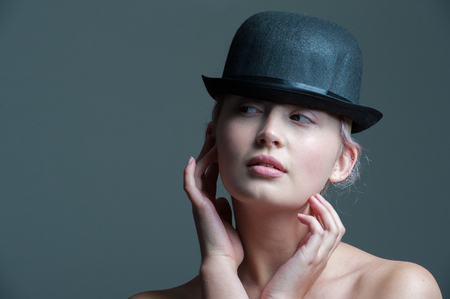 bowler hat: young lady posing in a black bowler hat with hands touching her face