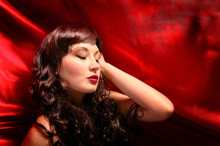 romance image: young lady with long brunette curled hair laying on red satin cloth Stock Photo