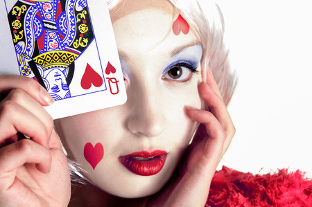 queen of hearts: young lady holding a playing card near her face with queen of hearts on card and face