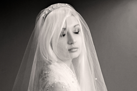 close up eyes: Close up portrait of bride under veil with eyes closed
