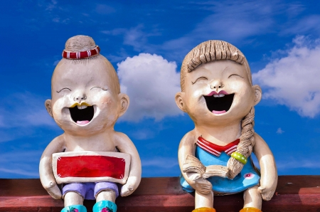 two childen figure laugh happily on blue sky background photo