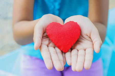 work heart: red heart on hand little girl Stock Photo