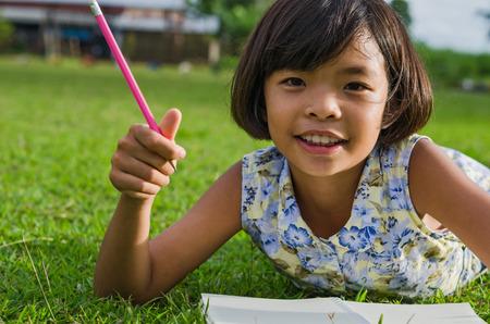 mignonne petite fille: Cute petite fille étudie à l'école et souriant et l'herbe verte