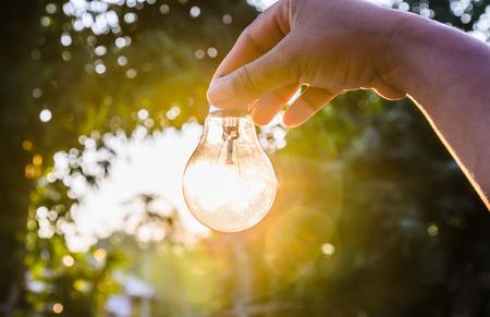 luz natural: y la celebraci�n de una bombilla de luz con el concepto de la energ�a puesta de sol