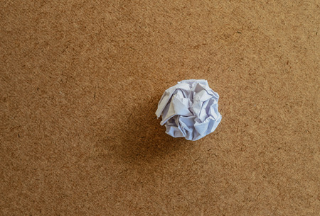 wad: crumpled a piece of paper on wood