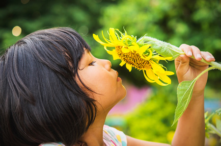 cute child with sunflower in nature