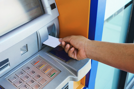 automatic transaction machine: mano femenina tarjeta de cajero automático en la inserción de cajero automático cajero automático para retirar dinero Foto de archivo