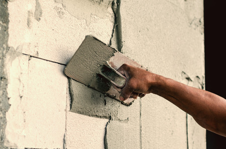 defects: Construction worker holding plastering trowel smoothing wall defects Stock Photo